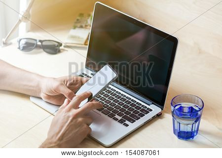 Silhouette of cropped shot of a young man working from home using smart phone and notebook computer man's hands using smart phone in interior man at his workplace using technology flare light