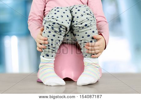 Children's legs hanging down from a chamber-pot on a blue background