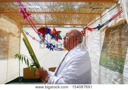 A Jewish man blesses on the four species in a Sukkah during the Jewish holiday of Sukkot. Sukkot is a Jewish holiday celebrated in late September to late October. The four species for Sukkot include etrog (citron) Hadass (boughs with leaves from myrtle tr