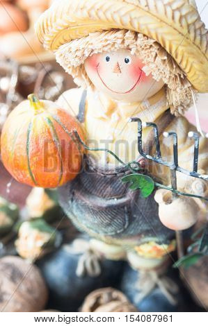 Farmer figurine with pumpkin and nuts. Halloween decoration.