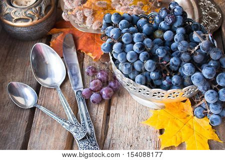 Old silver dish with grapes, spoons, autumn leaves on wood background