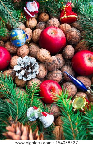 Christmas toys, nuts, fir cones, apples and twigs on a wooden background. Top view.