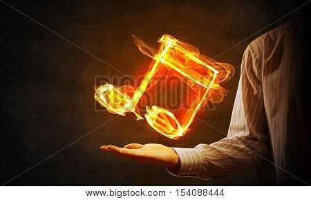 Close up of person hand holding fire music symbol