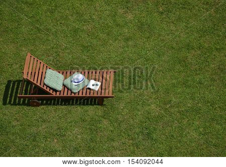 Wooden easy chair on a garden lawn with cushions book sunglasses and a hat