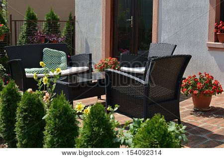 Set of brown garden furniture surrounded with garden plants