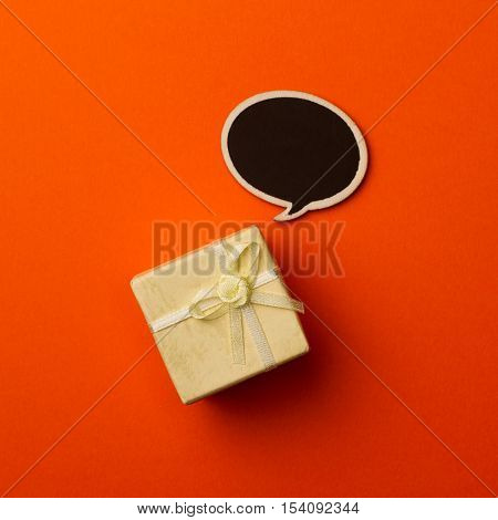 top view of small gift box on orange background with wooden black chalk board speech bubble for text