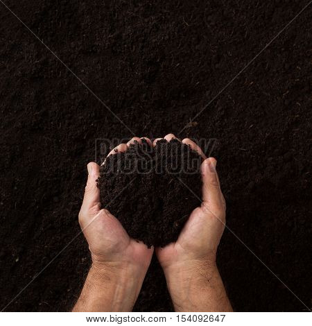 Top view of two hands holding soil over dark texture background
