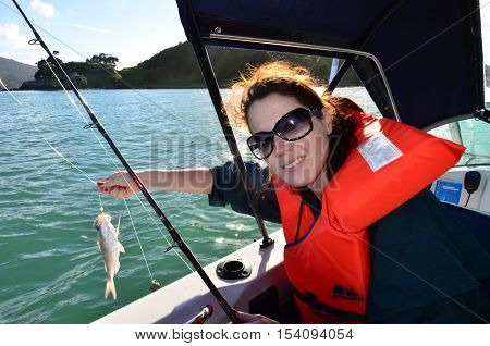 A woman holds a fish that she caught during fishing at sea on a fishing boat.