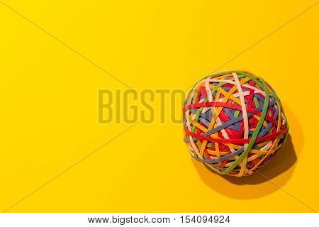 Colorful elastics made into a ball on a yellow background.