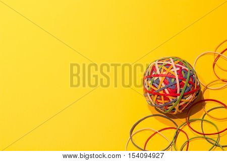 Multicolored elastic ball on a yellow background.
