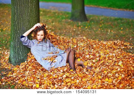 Pretty girl in a light purple cloak with downcast eyes lying on a pile of fallen autumn leaves in the forest leaning his head against the tree.