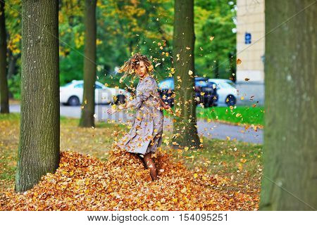 Cute attractive girl whirls and throws leaves in the air on the walk around the house a clear autumn day.