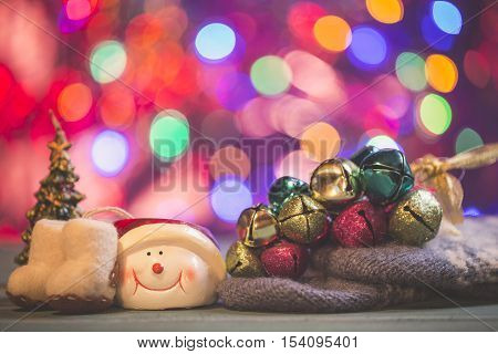 Christmas card composition with jingle bells gloves snowman felt boots and fir tree on lights background.