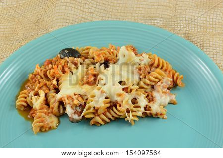 Casserole serving of whole wheat rotini pasta, ground turkey meat, cheese, sliced black olives and tomato sauce on plate