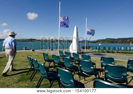 A New Zealander person (man) under the national flags of Australia and New Zealand during a National War Memorial Anzac Day services in New Zealand.
