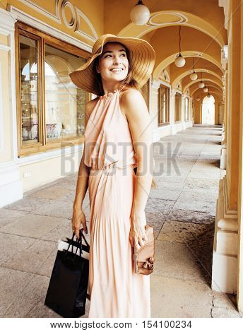 young pretty smiling woman in hat with bags on shopping at storefront, lifestyle real people concept close up