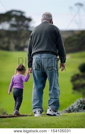 Grandfather walks and holds the hand of his grand daughter.