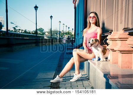 Hipster Fashion Girl and her Dog on Urban Background. Beautiful Woman in Sunglasses Outdoors with her Pet. Summer Street Style. Toned and Filtered Photo with Copy Space. Owner and Pets Concept.