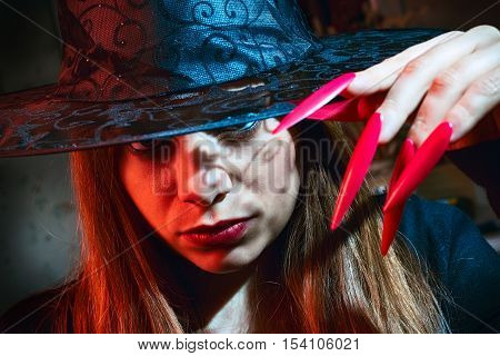 witch with red nails and black hat
