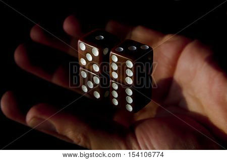 A mans hand throw casino dice during a gambling game.