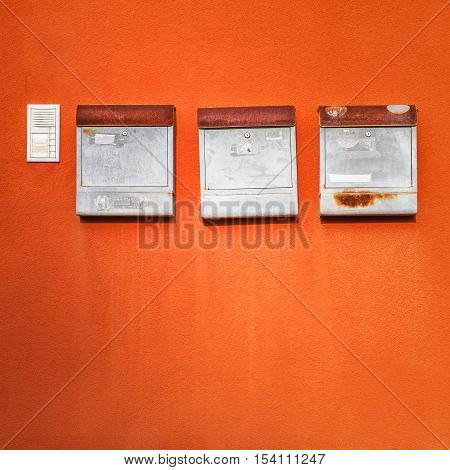 Old mailboxes on orange wall. Objects with clipping path. Copy space