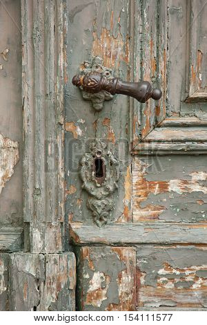 close-up part of the old dilapidated wooden door with handle and keyhole