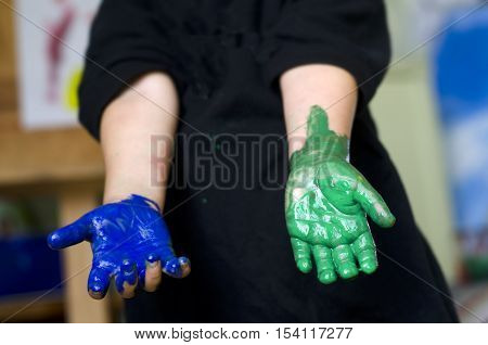 A Little girl with hands covered in blue and green paint