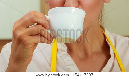 Woman Drinking Cup Of Coffee In Kitchen.
