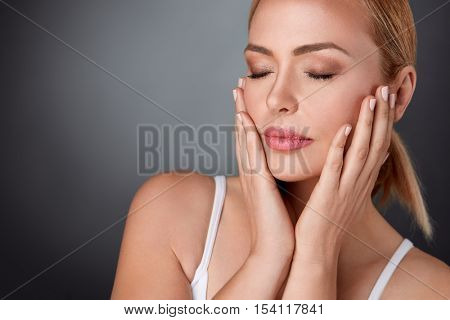 Beautiful middle aged woman touching her face, fresh healthy skin