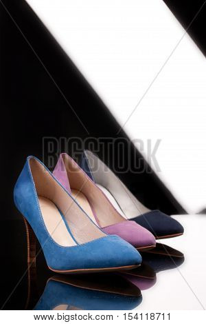 Different kinds of woman's shoes on a glass background