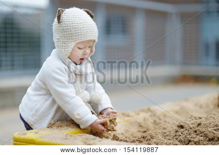 Adorable Toddler Girl Playing In A Sandbox