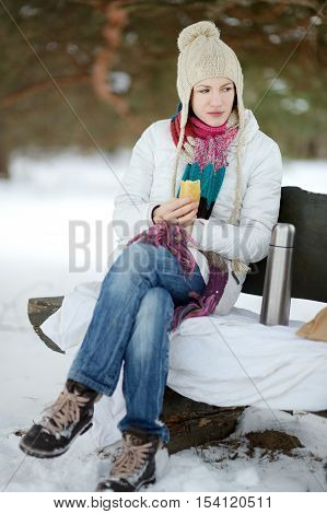 Young woman picnicking in the park at winter