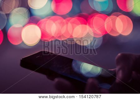 Smart phone in male hands in front of blurred city lights. Man typing on cell phone at night