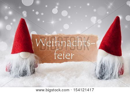 German Text Weihnachtsfeier Means Christmas Party. Christmas Greeting Card With Two Red Gnomes. Sparkling Bokeh And Noble Silver Background With Snow.