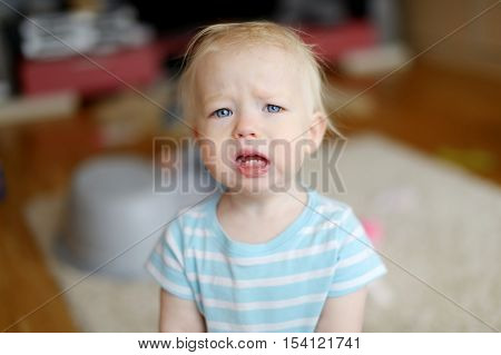 Angry upset toddler girl crying at home