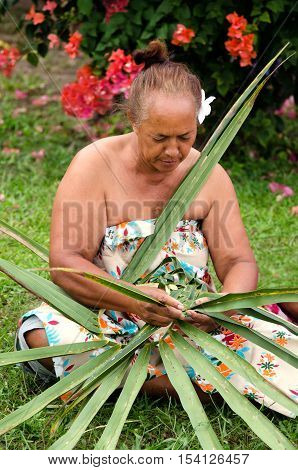Portrait of Polynesian Pacific Island Tahitian mature female weaving a hat knees out of palm leaves outside her home in Aitutaki lagoon Cook Islands.