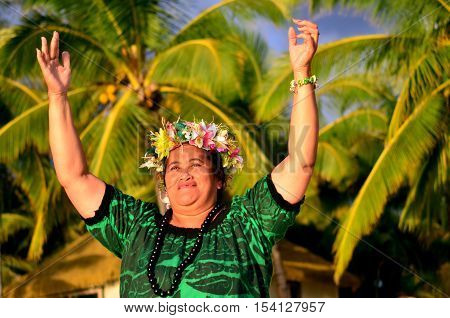 Portrait of happy smily mature Polynesian Pacific Islander woman on tropical beach with palm trees in the background.