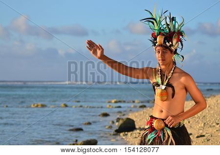 Portrait of attractive young Polynesian Pacific Island Tahitian male dancer in colorful costume dancing on tropical beach during sunset.