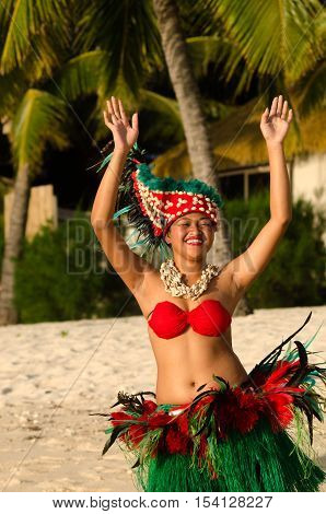 Portrait of Polynesian Pacific Island Tahitian female dancer in colorful costume dancing on tropical beach with palm trees in the background.