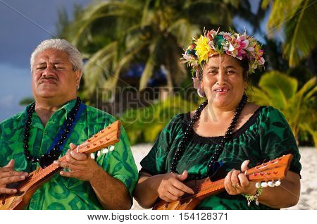 Portrait of two mature Polynesian Pacific islanders couple sing and plays Tahitian Music with Ukulele guitars on tropical beach with palm trees in the background.