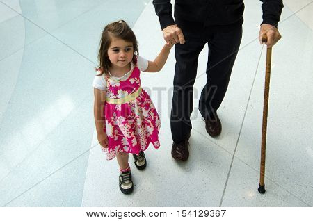 Littel Girl Helping And Supporting Her Great Grandfather