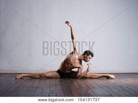 Handsome ballet dancer sitting on a splits. Warm up on the floor.