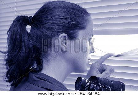 Young Woman Looking Through Blinds
