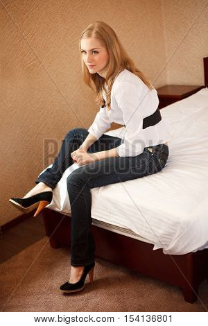 Young girl dressed in white blouse and jeans sits on the bed