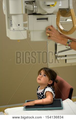 KAITAIA NZ - MAR 06: Little girl (Talya Ben-Ari age 3) during X-ray radiography on Mar 06 2014.X-ray is a common imaging test help doctors view the inside of body without having to make an incision.