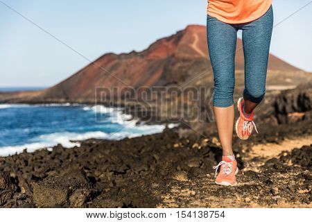 Trail running athlete woman runner legs and shoes lower body. Fitness woman jogging living active lifestyle jogging on rocky path in mountain nature landscape. Weight loss concept. Feet, legs closeup.