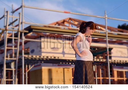Young pregnant woman worried outside here new home. Concept photo of buy a new home