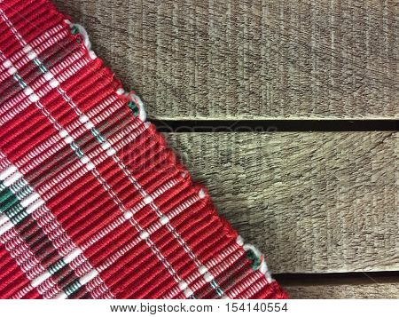 Christmas tablecloth on wooden background. empty table. old wooden planks with red, green and white checkered Christmas placemat. closeup, texture. copy space for your text
