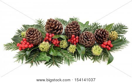 Winter flora and christmas decoration of holly with red berries, ivy, pine cones and  fir over white background.