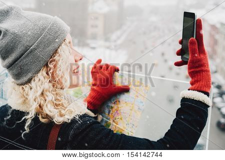 Young blond curly female tourist in warm clothes and red gloves with London map making selfie standing on the roof of winter city blurred road with cars in background